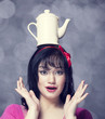 Brunette women with teapot on head.