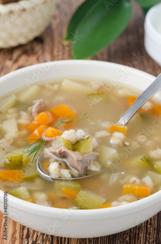 Russian soup rassolnik in a white bowl, spoon of soup closeup
