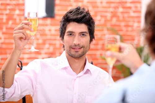 Two businessmen drinking champagne in restaurant