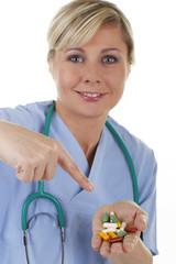 Junge Ärztin deutet auf eine Handvoll Tabletten
