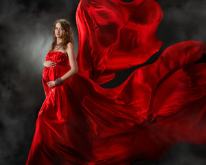 Pregnant woman in red flying dress