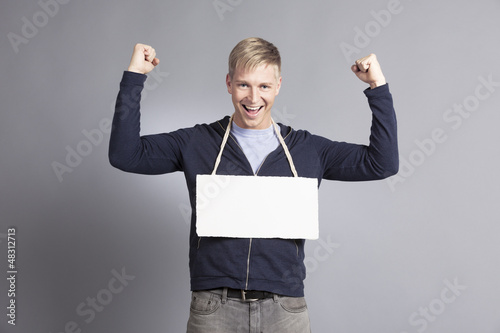 Joyous successful man presenting empty signboard.