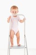 Impish little girl standing on top of ladder
