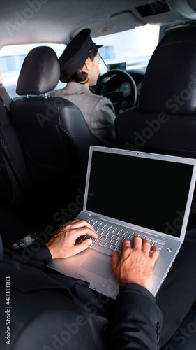 Businessman working on laptop in limousine