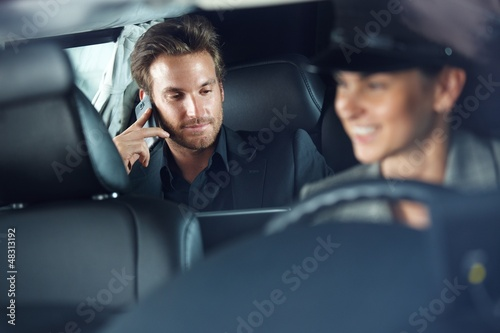 Businessman in limousine chauffeur driving