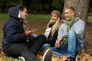 Young friends sitting on ground in autumn park