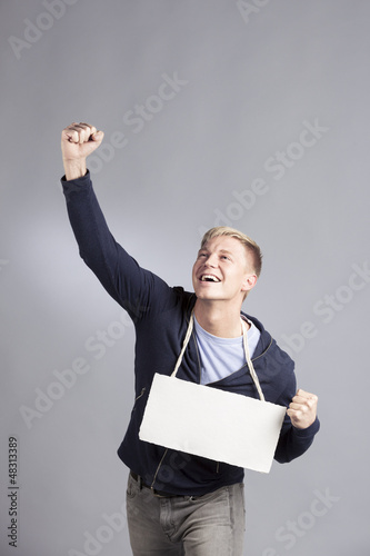 Overjoyed successful man presenting blank signboard.