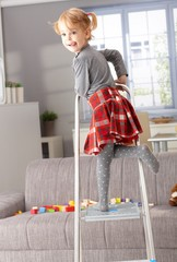 Cute 3 year old posing on ladder in living room