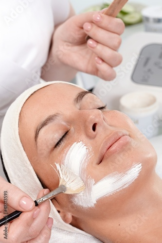 Applying facial cream by brush