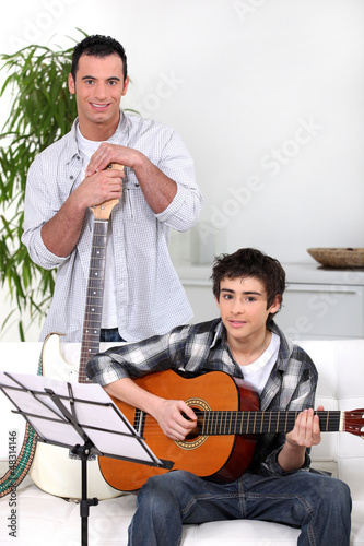 Man teaching teenage boy the guitar