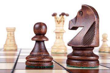 Schachfiguren auf Spielfeld (Pferd und Bauer im Vordergrund)