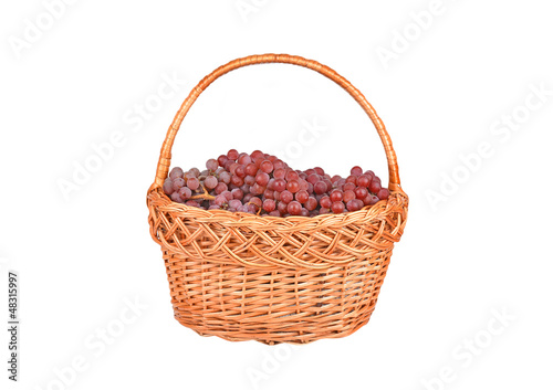 Red grape in a wattled basket, isolated on a white background