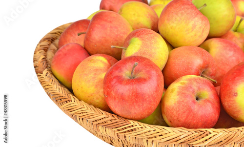 Red apple in a wattled basket, isolated on white background