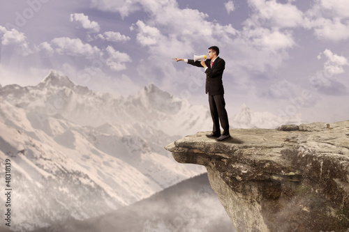 Businessman using speaker on cliff