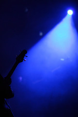 silhouette guitar player blue stage lights