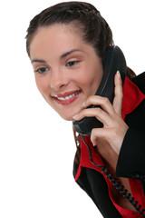 Brunette using land-line telephone