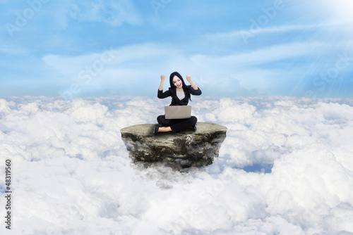 Happy businesswoman above clouds
