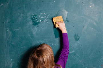 Young girl wiping chalkboard with wet sponge