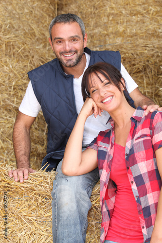 Farming couple sitting on hay