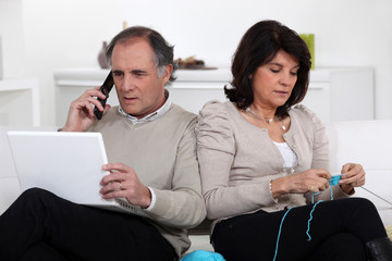 Man on phone and woman knitting at home
