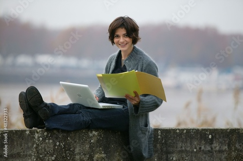 Woman studying whilst sat on a wall