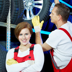 Two car mechanics store winter tires for tire changing