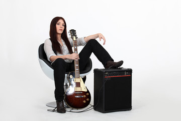 Woman with foot on an amplifier and holding guitar