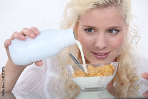 Woman pouring milk into cereal bowl