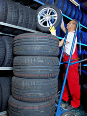 Car mechanics looking for a tire in a tire warehouse