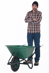 Tradesman standing behind a wheelbarrow