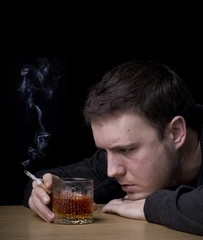 man looking at a glass of whiskey and smoking