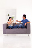 young couple playing rock-paper-scissors game at home