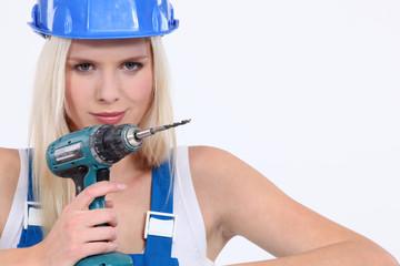 Blond female builder holding cordless drill