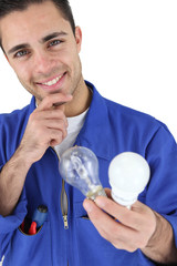 Young electrician smiling holding light bulbs
