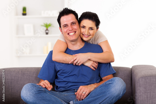 young loving couple hugging on sofa at home