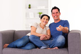 young couple watching comedy at home