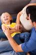 parents tickling little daughter on sofa