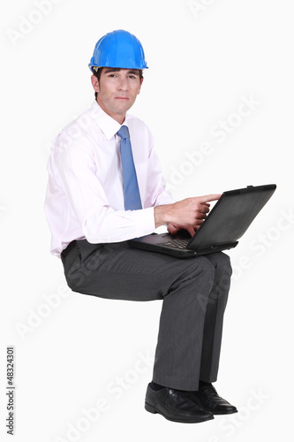 Engineer sitting in empty copyspace with a laptop