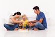 young family playing with educational toy on bedroom floor