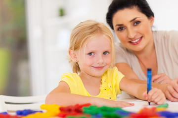 cute little girl drawing with mother at home