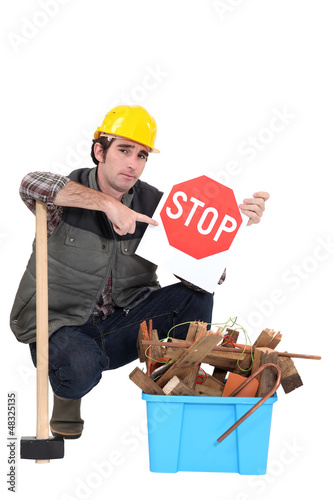 Labourer holding a stop sign while squatting