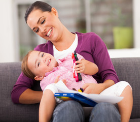 happy mother playing with little daughter at home