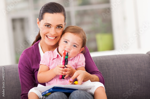 happy mother and little daughter with crayon at home