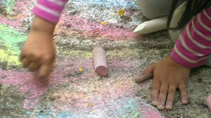Child Painting with Colorful Chalk on the Pavement