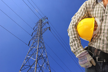 Electrician and high voltage power pylon against blue sky
