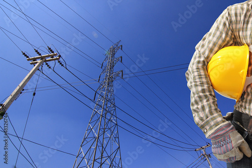 Electrician and  high voltage power transmission line tower with