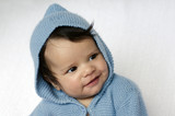 Newborn baby wearing blue cardigan smiles