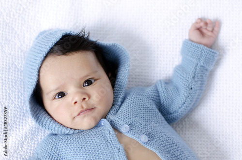 Newborn baby wearing blue cardigan