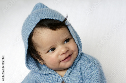 Newborn baby wearing blue cardigan smiles