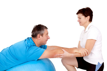 Woman helps man when practicing with the exercise ball